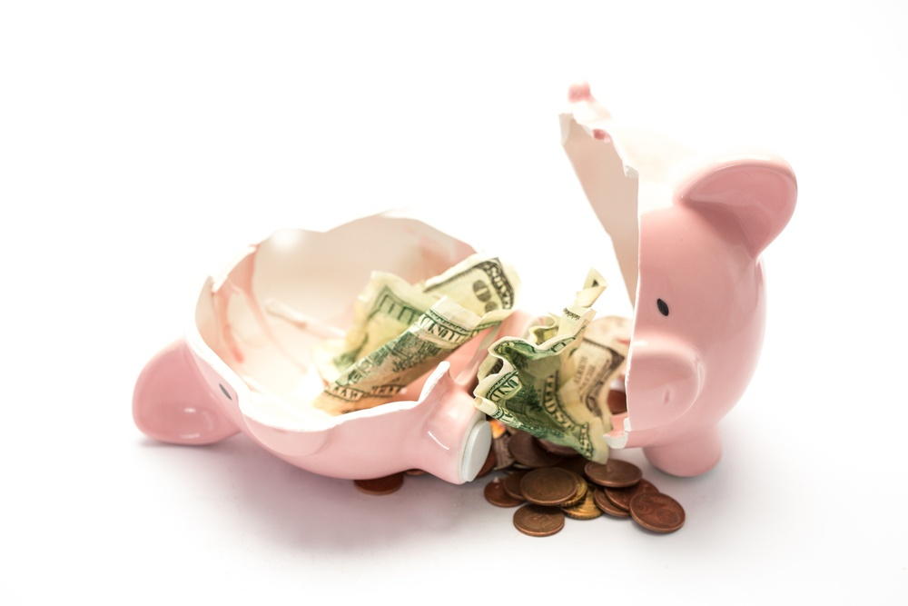 Piggy bank broken with money inside on white background.jpeg